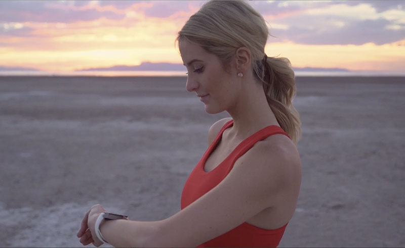 """Pretty """"influencer"""" with a smart watch framed by a sunset"""